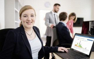 Lächelnde Frau vor dem Laptop